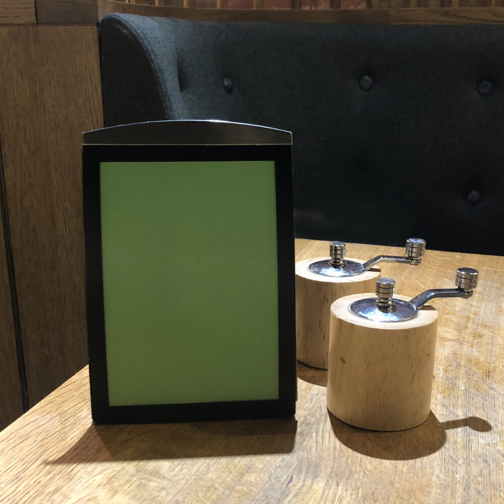A6 black magnetic menu holder in situ at a restaurant at London Gatwick