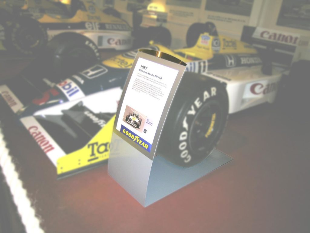 Our tabletop sign-holder design is scaled up to fit around the wheel of a racing car.